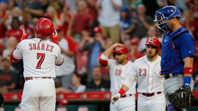 Cincinnati Reds third baseman Eugenio Suarez (7) crosses the plate on a 2-run home run in the fifth inning of the MLB National League game between the Cincinnati Reds and the Chicago Cubs at Great American Ball Park in downtown Cincinnati on Friday, June 22, 2018. The Reds won 6-3.