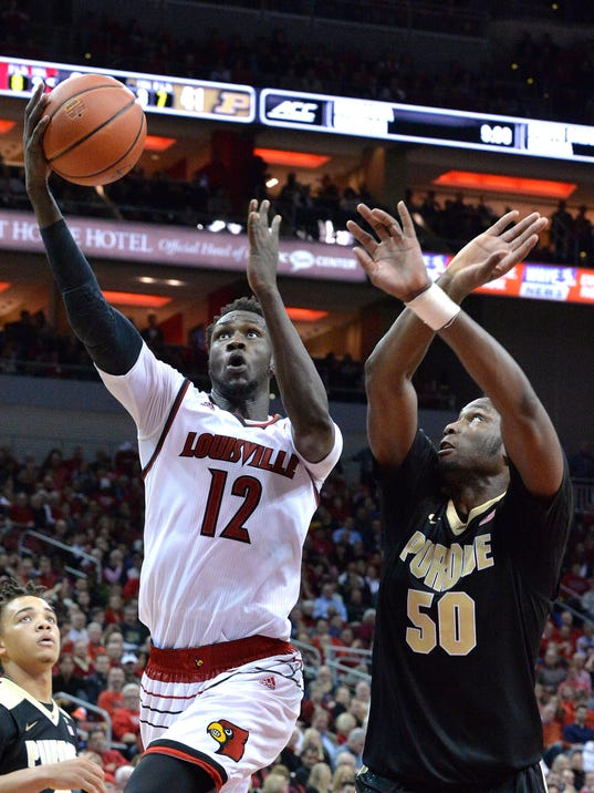 Louisville's Mangok Mathiang (12) goes in for a layup past the defense of Purdue's Caleb Swanigan (50) during the second half of an NCAA college basketball game, Wednesday, Nov. 30, 2016, in Louisville, Ky. Louisville won 71-64. (AP Photo/Timothy D. Easley)