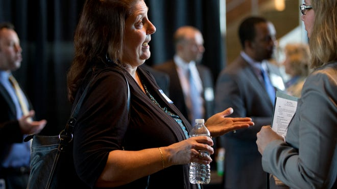 Anita Wilson of Gold Canyon (left) speaks with Mary Fisher, team leader for client services at Edward Jones, during a job fair held by the investment firm this month in Tempe. Arizona jobs continue to make gains, but very slowly.