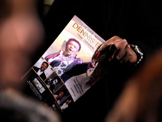 An attendee holds as copy of the Dennis Edwards Memorial