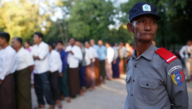 A police officer stands guard as voters queue up outside a polling station in Mandalay, Myanmar, Sunday, Nov. 8, 2015. Myanmar voted Sunday in historic elections that will test whether popular mandate will help loosen the military's longstanding hold on power even if opposition leader Aung San Suu Kyi's party secures a widely-expected victory.