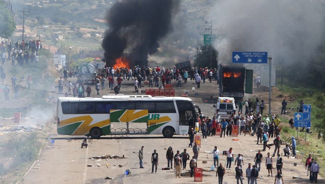 Protesting teachers who were blocking a federal highway hold their positions with a passenger bus across the road and burning trucks as they battle with riot police in the state of Oaxaca, near the town of Nochixtlan, Mexico, on Sunday.