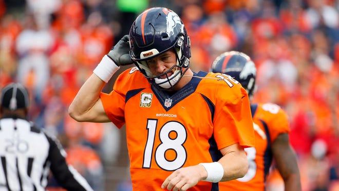 Denver quarterback Peyton Manning removed  his helmet after throwing one of his four interceptions Sunday against Kansas City.