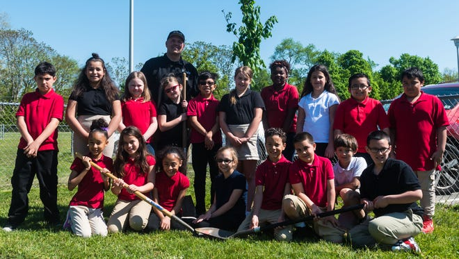 D'Ippolito Elementary School physical education teacher John Capizola's third-grade class poses for a photo after planting a maple tree at D'Ippolito Elementary School on Tuesday, May 8.