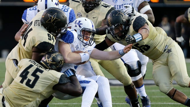 Kentucky quarterback Drew Barker, center, is brought down for a 1-yard loss by a group of Vanderbilt defenders in the first half of an NCAA college football game Saturday, Nov. 14, 2015, in Nashville, Tenn.