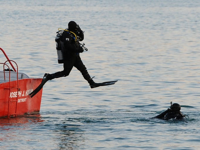 Divers jump into the Detroit River to connect a line