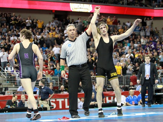Mar 23, 2013; Des Moines, IA, USA;   Derek St. John of Iowa (in black) celebrates his win over Jason Welch of Northwestern (in purple) in the 157 lb finals in the NCAA wrestling Division I championship at Wells Fargo Arena. St. John beat Welch 3-2.  Mandatory Credit: Reese Strickland-USA TODAY Sports