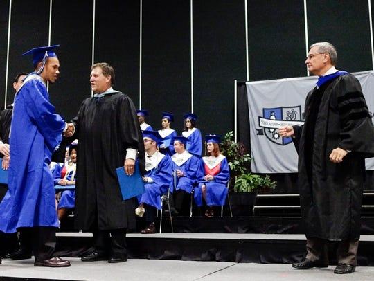 Principal Jeffrey Debetaz hands out diplomas to students