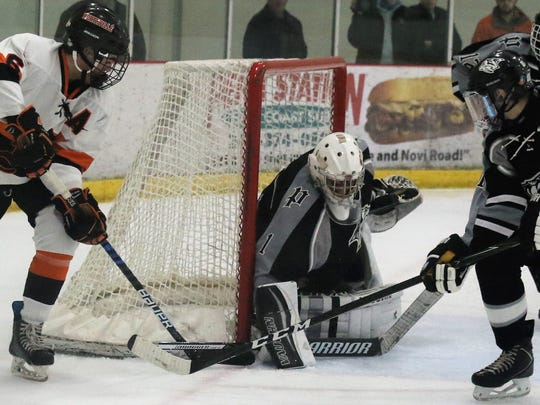 Plymouth goalie Brenden Olepa (No. 1) denies a Northville player trying to jam the puck in at the left post during Friday's game at Novi Ice Arena.