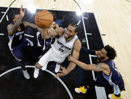 San Antonio Spurs forward Kawhi Leonard (2) is fouled as he drives to the basket between Memphis Grizzlies defenders JaMychal Green, left, and Mike Conley (11) during the second half of Game 5 in a first-round NBA basketball playoff series, Tuesday, April 25, 2017, in San Antonio. San Antonio won 116-103. (AP Photo/Eric Gay)