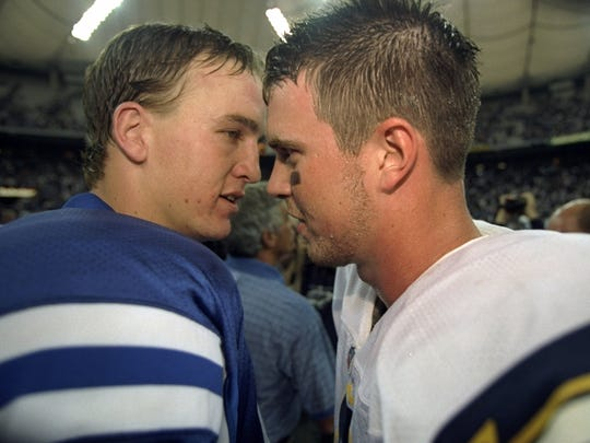 Quarterback Ryan Leaf #16 (R) of the San Diego Chargers and quarterback Peyton Manning #18 (L) of the Indianapolis Colts converse following a game at the RCA Dome in Indianapolis, Indiana. The Colts defeated the Chargers 17-12.
