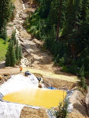 A worker stands near a temporary diversion pond containing