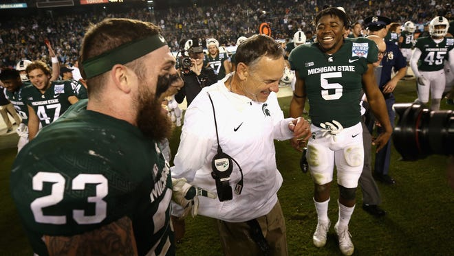 MSU's Chris Frey, left, and Andrew Dowell, right, congratulate head coach Mark Dantonio after Thursday night's 42-17 win over Washington State in the Holiday Bowl win, which was also Dantonio's 100th win at MSU.
