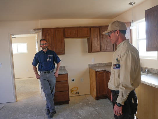 San Juan College School of Trades and Technology coordinator Chad Triplett, left, and instructor Zack Pettijohn show off one of the homes to be auctioned on Tuesday at San Juan College in Farmington.