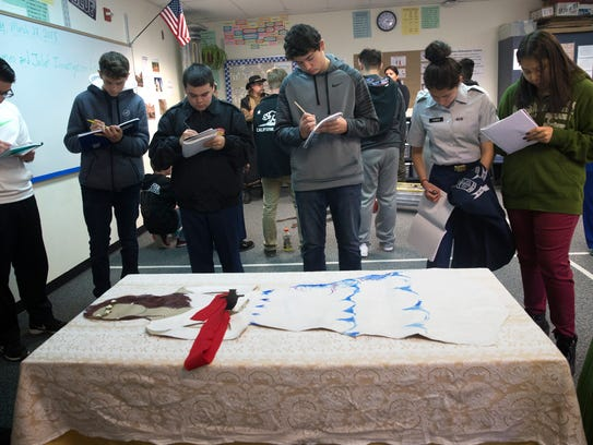 """Crime scene investigators and detectives from the Farmington Police Department and San Juan County Sheriff's Office help Piedra Vista High School freshmen investigate a simulated death scene from Shakespeare's """"Romeo and Juliet"""" on Wednesday at Piedra Vista High School in Farmington."""