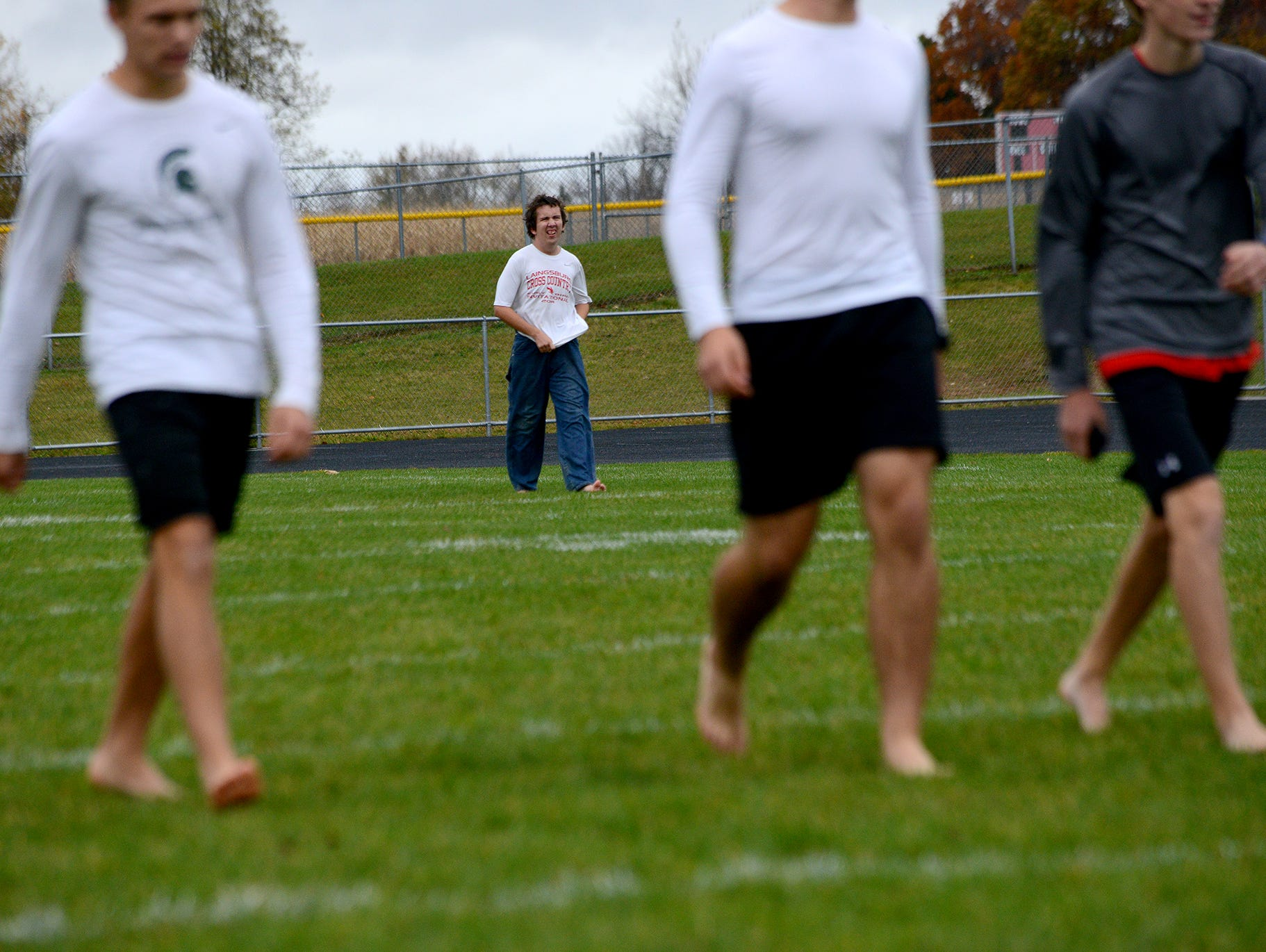 """Ray Latchaw practices with his teammates on the Laingsburg cross country team Wednesday, October 28, 2015 at Laingsburg High School. Latchaw, a junior, is autistic, but runs, he says, to stay healthy and because he enjoys the """"me time"""" he gets."""