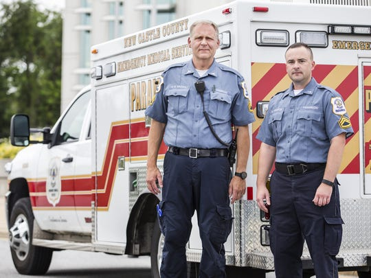 New Castle County EMS Senior Corporals Paul Bazzoli (left) and Brian Warrick pose for a portrait with a Paramedic response vehicle on Tuesday afternoon.