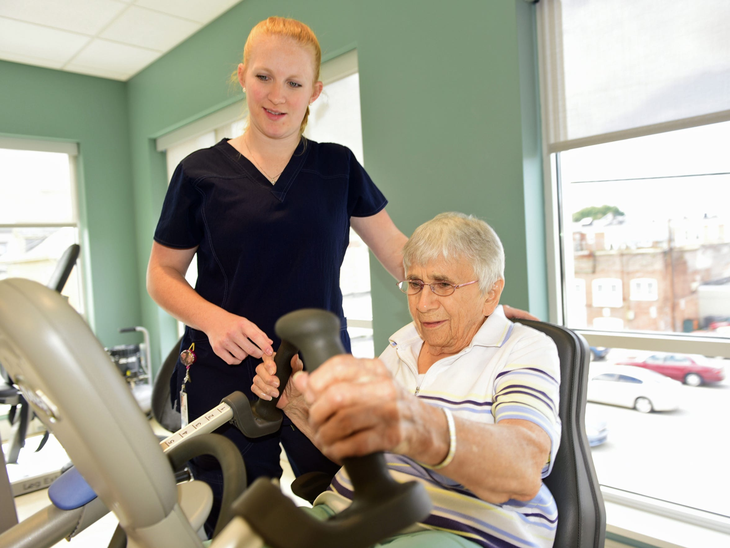 Paige Wright, left, physical therapy assistant, helps