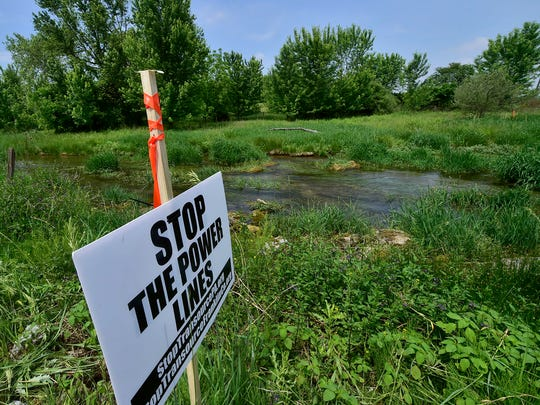 A sign opposing the power line sits at Falling Spring Creek. Officials from the Public Utility Commission visit the Tim Cook Memorial Cross Country Course at Falling Spring Elementary School on Tuesday, May 29, 2018.  A proposal is in the works  for the Transourse high voltage power line to cross near the property.
