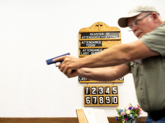 Reid Crosby practices with a fake gun at Calvary Baptist Church in New Stanton, Pa.,  on Friday, June 22, 2018.   Representatives from 13 area churches got tips last week on proper handling of guns in the event any of their congregations faces a deadly intruder. In an age when any house of worship might become a gunman's target, the 17 men who gathered at Calvary Baptist Church in New Stanton practiced the best grip and stance to use when aiming a handgun. (Carolyn Rogers/Pittsburgh Tribune-Review via AP)