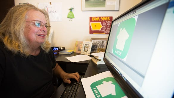 Mary Armstrong checks her neighborhood online social media network, Nextdoor Four Hills. Here she is printing stencil copies of the Nextdoor Four Hills logo for members to paint on their curbs, making it easier to connect in person, as well as online and with phone and tablet apps.  Credit: Anayssa Vasquez/Sun-News
