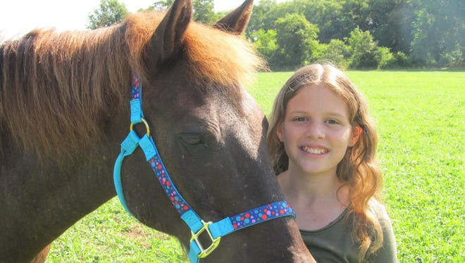 Alyssa Jastram, 11, with her aged Chincoteague pony, Tunee.