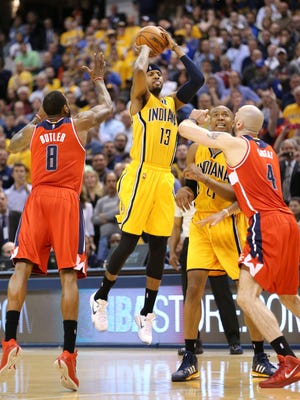 Indiana Pacers forward Paul George fires a shot over Washington Wizards forward Rasual Butler, left, and center Marcin Gortat to tie the game 85-85 and send the game into double overtime. The Pacers beat the Washington Wizards 99-95 in double overtime at Bankers Life Fieldhouse on Tuesday, April 14, 2015.