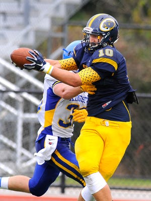 DeWitt tight end Evan Conn makes a fingertip catch on a pass from quarterback Will Nagel for a first down past Kingsford's Sam Santi Thursday 9/3/2015.  Second of a two-picture series.