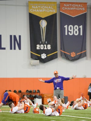 Clemson's new National Championship banner hangs behind head coach Dabo Swinney as he has some fun during the Tigers opening day of spring practice on Wednesday, March 1, 2017.