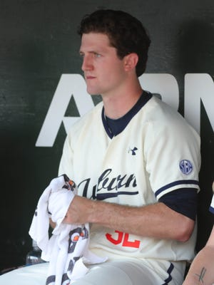 Auburn pitcher Casey Mize sits in the dugout before action against LSU Friday, May 18, 2018, at Hitchcock Field at Plainsman Park in Auburn, Alabama.