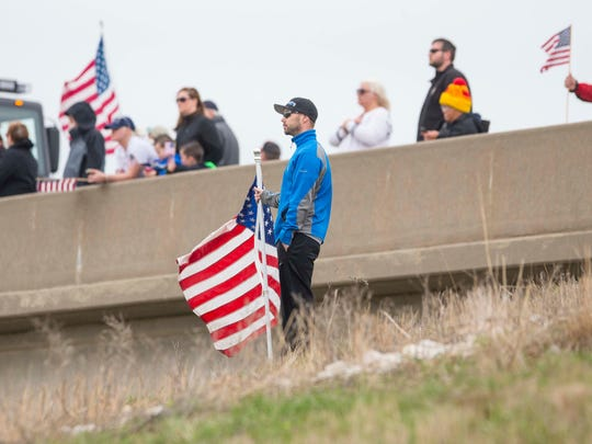 Jake Soll of Johnston watches the funeral procession on the 86th Street overpass over I-80/I-35 to pay respects to police officer Susan Farrell, Des Moines Police Dept.  Wednesday March 30, 2016, after her funeral at Lutheran Church of Hope in West Des Moines.