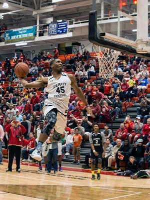 Louisville recruit Donovan Mitchell takes flight during the dunk contest at the 2015 Kentucky Derby Festival Basketball Classic at New Albany High School on Friday night. 4/10/15