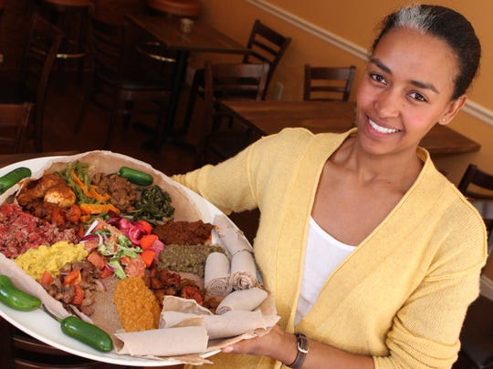 Owner Selamawit Tesfaye holds a dish with a sample of the menu at Lalibela Ethiopian Cuisine, photographed April 30, 2010 in Mount Kisco. Lalibela is the first Ethiopian restaurant to open in the region. ( Tania Savayan / The Journal News )
