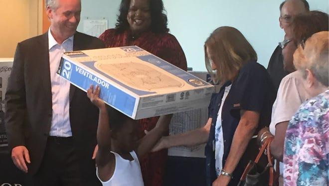 Louisville Mayor Greg Fischer helps pass out fans at Bridges of Neighborhood Place on Wednesday.