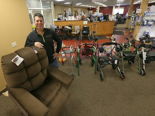 Ron Nettnin, owner of Westside Medical Supply in Gates, stands on the showroom floor with a lift chair Friday, Nov. 11, 2016.