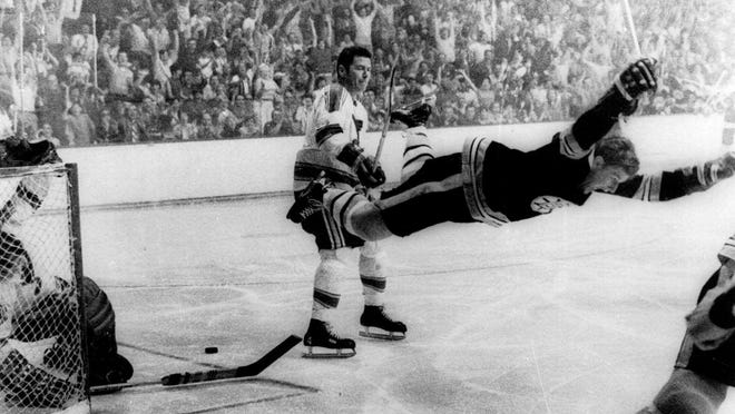 Boston Bruins' Bobby Orr flies through the air after scoring the winning goal past St. Louis Blues' goalie Glenn Hall during overtime of the Stanley Cup finals in Boston on May 10, 1970.