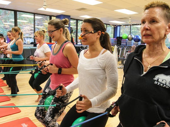 Far right, Jill Carlson, instructor Becky Leonard, Brittany Singer, and others participate in a barre fusion class at Black Bear Fitness.