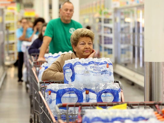 Corpus Christi residents stand in line to pay for cases of water after City of Corpus Christi officials confirmed Thursday morning that one chemical contaminated the city's water supply on Thursday, Dec. 15, 2016, at an H-E-B store in Corpus Christi.