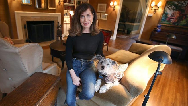 Jill Harmon with her Chinese crested, Fabio, in the living room of her century-old Tudor Revival home in the Summit Hill neighborhood of Minneapolis.