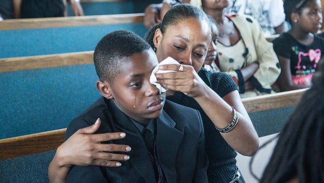 Sharon Lamb with her son Kasai Hayden, 10, extended family of deceased Michelle Cusseaux, mourns their loss during the funeral services