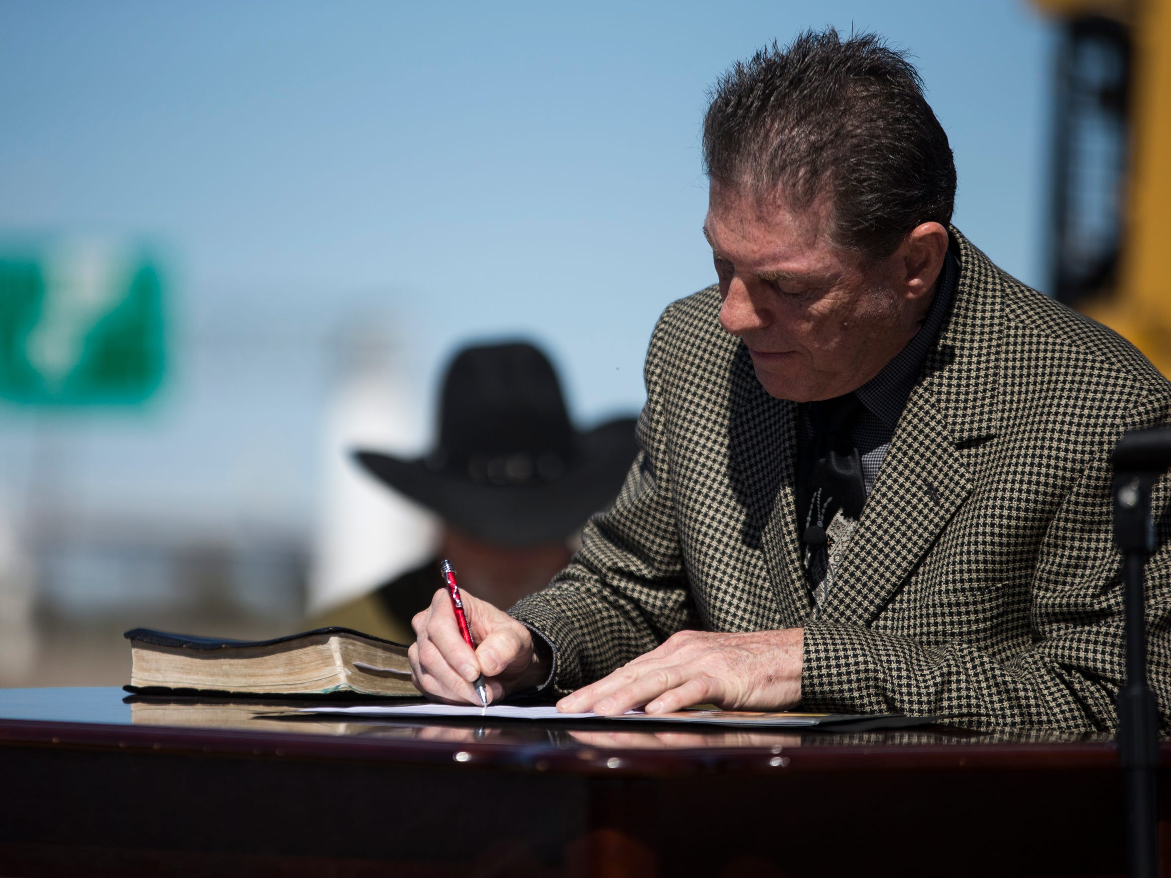 Pastor Richard Milby signs a contract to start construction on the base of the Corpus Christi Cross during a ceremony Monday, Jan. 29, 2018, near Carbon Plant Road and Interstate 37.