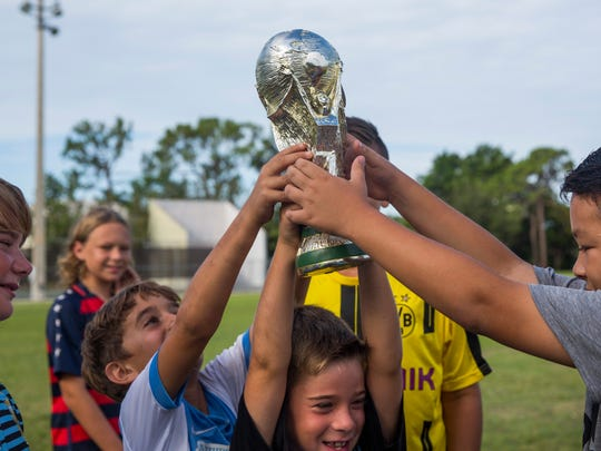 Nolan Bruno, center, tightly grasps a toy World Cup trophy with help from Sam Pino, right, and Christian Pocialik during Kick-Off Soccer's summer day camp at the Seagate Park in Naples Friday, June 15, 2018.