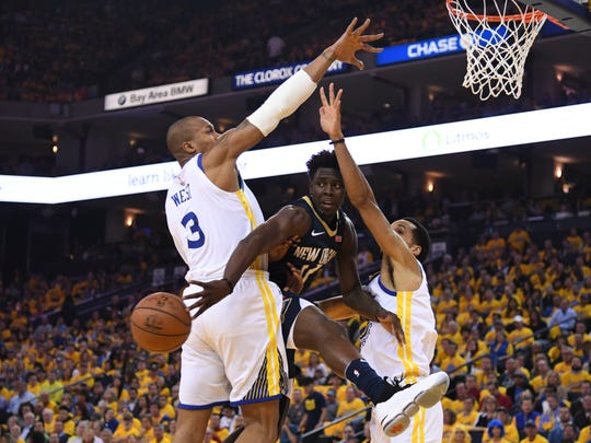 May 8, 2018; Oakland, CA, USA; New Orleans Pelicans guard Jrue Holiday (11) passes the basketball against Golden State Warriors forward David West (3) and guard Shaun Livingston (34) during the first quarter in game five of the second round of the 2018 NBA Playoffs at Oracle Arena. Mandatory Credit: Kyle Terada-USA TODAY Sports