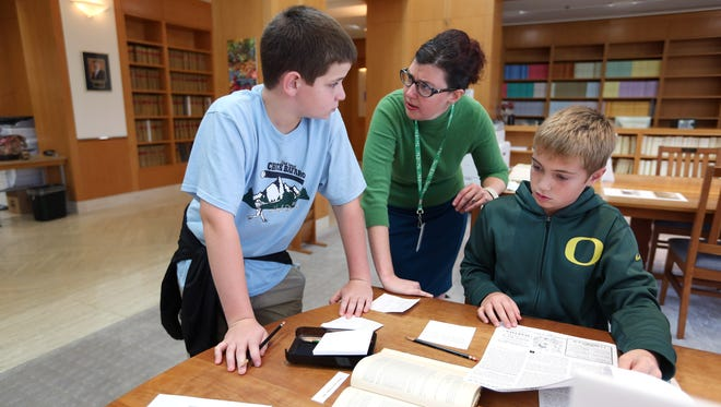 Theresa Rea helps Gavin Reed, 12, and Joey Borregard, 12, with the Murder Mystery Tour during an open house and scavenger hunt Saturday, Oct. 31, 2015, at the Oregon State Archives in Salem, Ore.
