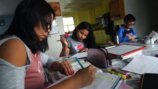 DACA student Maria Roberto, left, does her homework