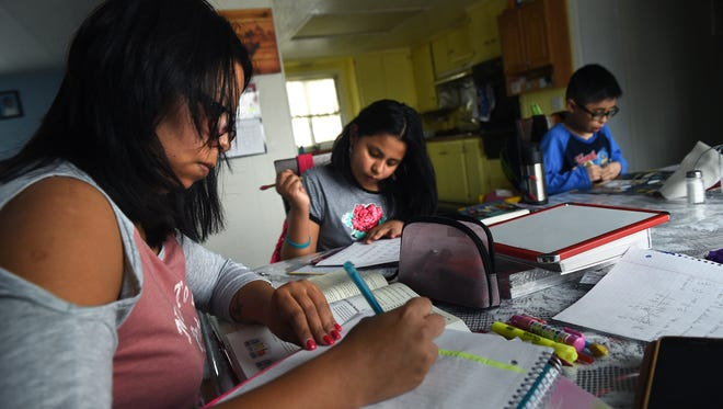 DACA student Maria Roberto, left, does her homework along side her children Ashlee Romano, middle, and Gerardo Mederos, after picking them up from school in Reno on Feb. 7, 2017.