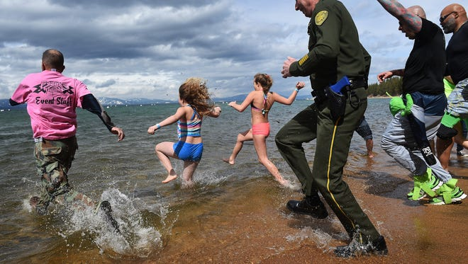 Brave swimmers, including members of multiple law enforcement agencies, rush into the water during the 2017 Polar Plunge benefit for Special Olympics at Zephyr Cove on Lake Tahoe.