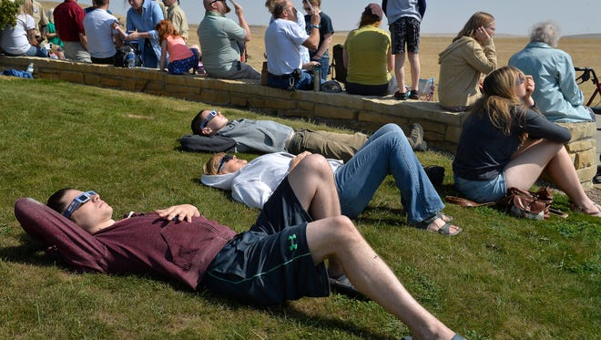 People watch the 2017 solar eclipse from the First People's Buffalo Jump State Park visitors center on Monday morning.