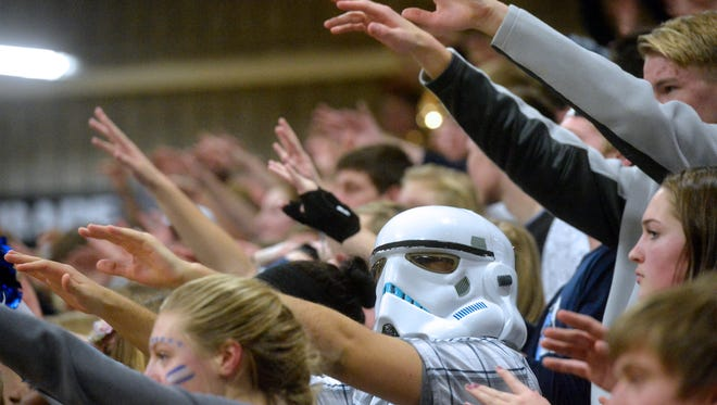 Great Falls High fans wiggle their fingers in the air during a Bison freethrow attempt in Tuesday's crosstown basketball game against CMR.