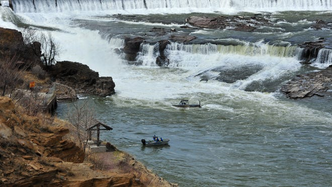 A boat from the Cascade County Sheriff's Office aided by a boat from Cascade County Search and Rescue patrol the waters below Black Eagle Falls at Black Eagle Dam on Monday afternoon as they search for the body of a person who was washed over the dam on Monday morning.